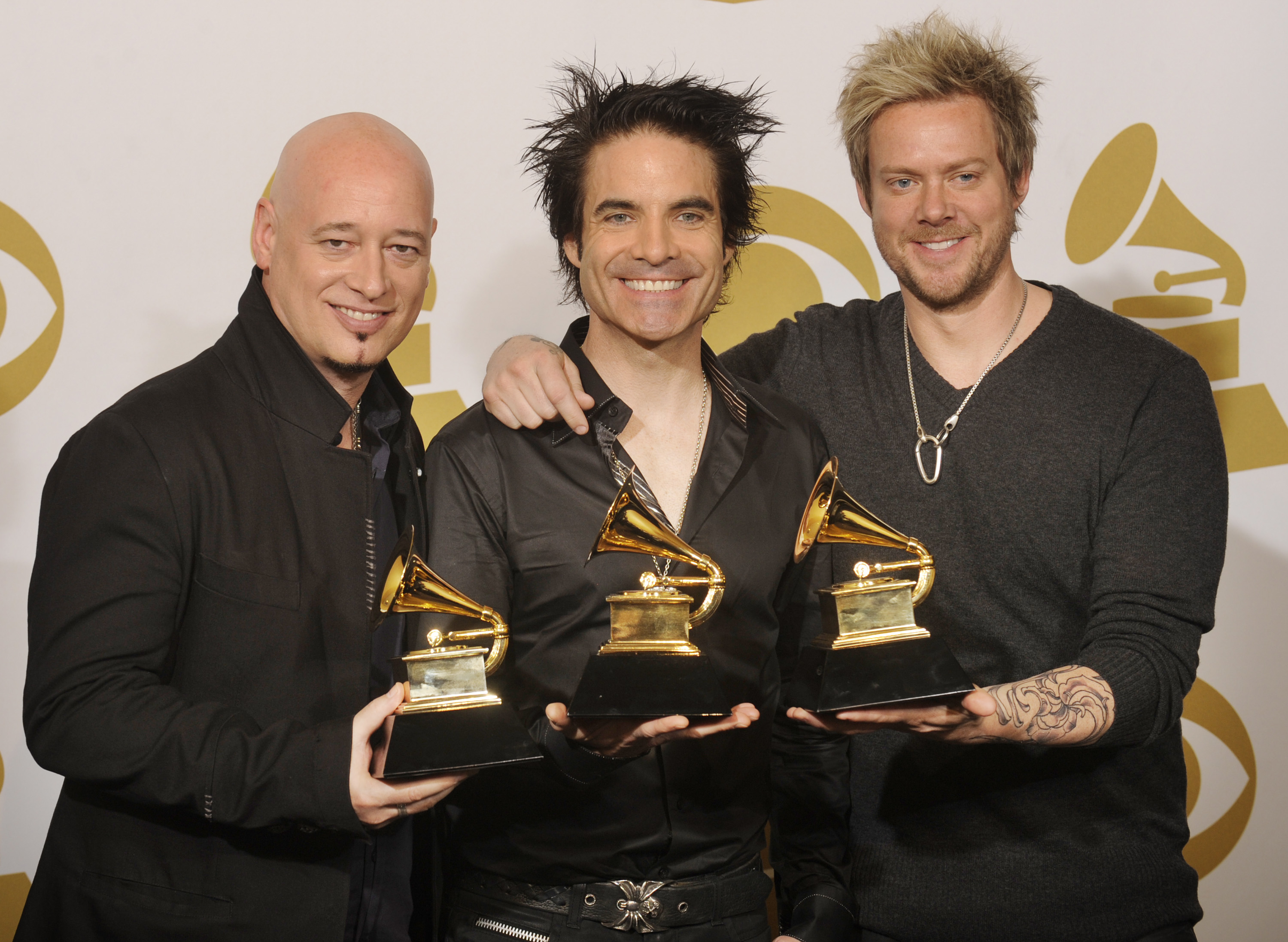 The band Train hold their award for Best Pop Performance By A Duo Or Group With Vocals at the 53rd Grammy Awards in Los Angeles